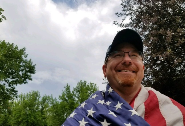 Martin C. Fredricks IV draped in American flag.